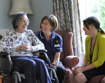 Smiling care home resident, nurse and visitor.